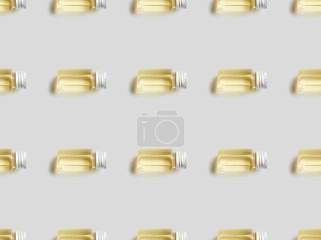 Photo pour Vue de dessus des bouteilles avec de l'huile essentielle sur fond gris - image libre de droit