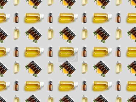 Photo for Pattern with bottles of organic essential oil and sliced orange on grey - Royalty Free Image