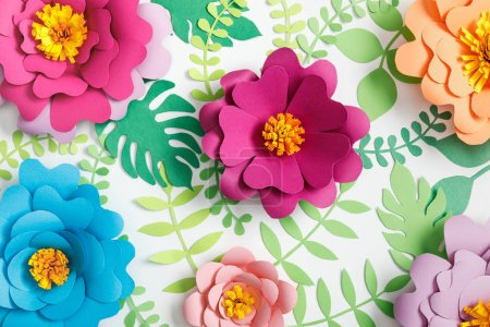 Photo for Top view of pink, purple, orange, blue paper flowers and green leaves on white background - Royalty Free Image