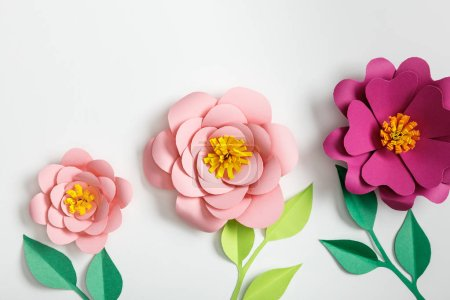 Photo for Top view of pink paper flowers and green plants with leaves on grey background - Royalty Free Image