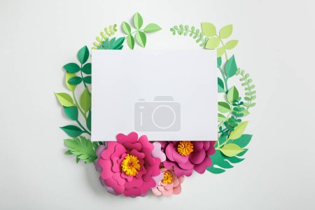 Photo for Top view of white blank card near pink paper flowers with green leaves on grey background - Royalty Free Image