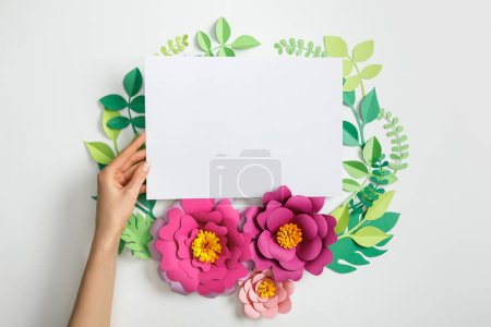 Photo for Cropped view of woman putting white blank card near pink paper flowers and leaves on grey background - Royalty Free Image