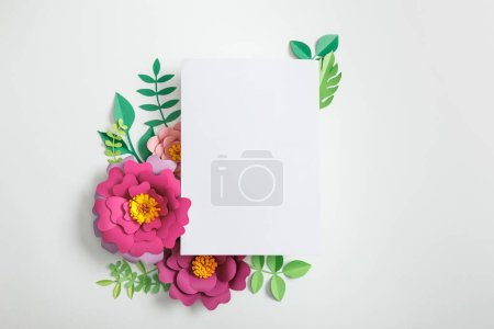 top view of white blank card near pink paper flowers and green leaves on grey background