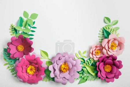 top view of pink and lilac paper flowers and green plants with leaves on grey background