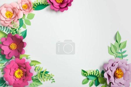 Foto de Vista superior de flores de papel multicolores y plantas verdes con hojas sobre fondo gris - Imagen libre de derechos