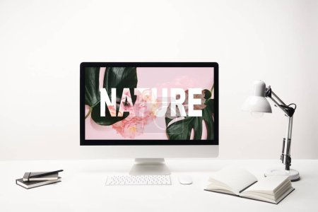 Photo for Computer with nature lettering and green tropical leaves and roses on monitor on desk on white background - Royalty Free Image