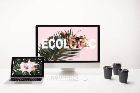 Foto de Ordenador con letras ecológico en monitor y ordenador portátil con el deletreado de eco en pantalla en el escritorio con las tazas de papel sobre fondo blanco - Imagen libre de derechos