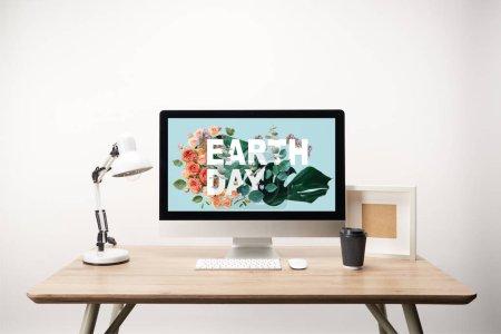 Photo pour Ordinateur avec feuilles et fleurs de monstère verte et lettrage de jour de terre sur moniteur sur bureau en bois - image libre de droit