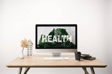 Photo for Computer with green leaves and health lettering on monitor on wooden desk - Royalty Free Image