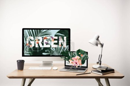 Photo for Computer with green lettering and monstera leaves illustration on monitor on wooden table - Royalty Free Image