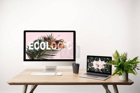 Photo for Computer with ecologic illustration on monitor and laptop with monstera leaves and eco lettering on screen on wooden table - Royalty Free Image