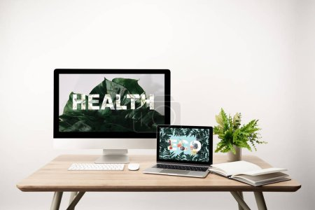 Photo for Computer with health illustration and monstera leaves on monitor and laptop with eco lettering and fern leaves on screen on wooden table - Royalty Free Image