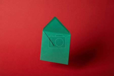 Photo for Bright, empty and green envelope on red background with copy space - Royalty Free Image