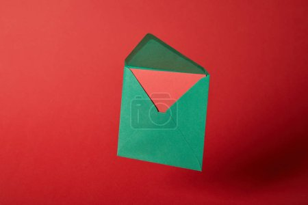 Photo for Bright,and green envelope with card on red background with copy space - Royalty Free Image