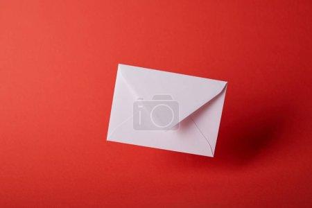 Foto de Sobre blanco y vacíelo sobre fondo rojo colorido con espacio de copia - Imagen libre de derechos