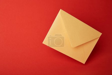 Photo for Bright, colorful and yellow envelope on red background with copy space - Royalty Free Image