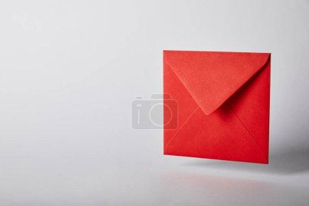 Foto de Sobre rojo y brillante sobre fondo gris con espacio de copia - Imagen libre de derechos