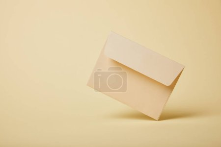 Photo for Beige and pastel envelope on yellow background with copy space - Royalty Free Image