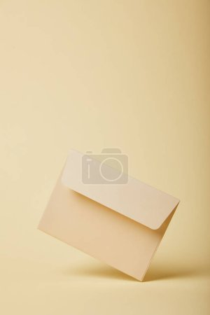 Photo for Beige and empty envelope on yellow background with copy space - Royalty Free Image