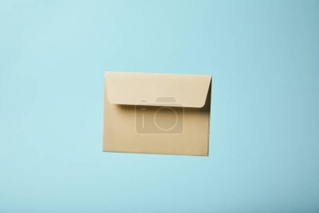 Photo for Beige and blank envelope on blue background with copy space - Royalty Free Image