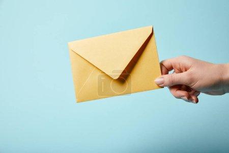 Photo pour Vue recadrée de la femme tenant une enveloppe jaune et brillante sur fond bleu - image libre de droit
