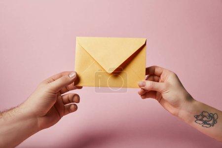 Photo pour Vue partielle de la femme avec le tattoo et homme tenant une enveloppe jaune sur fond rose - image libre de droit