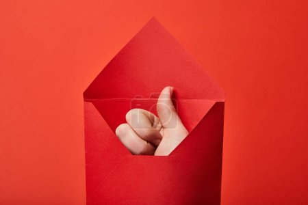 Photo for Partial view of man showing thumb up in bright envelope on red background - Royalty Free Image