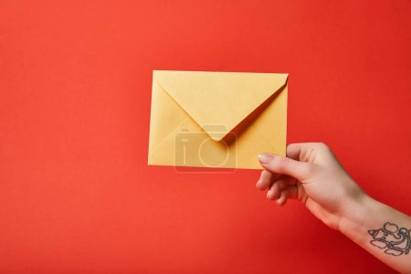 Photo for Partial view of woman with tattoo holding yellow envelope on red background - Royalty Free Image