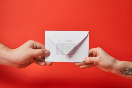 Photo for Cropped view of woman with tattoo and man holding white envelope on red background - Royalty Free Image