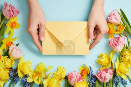 Photo for Partial view of female hands with yellow envelope, pink tulips, yellow daffodils and blue hyacinths on blue - Royalty Free Image