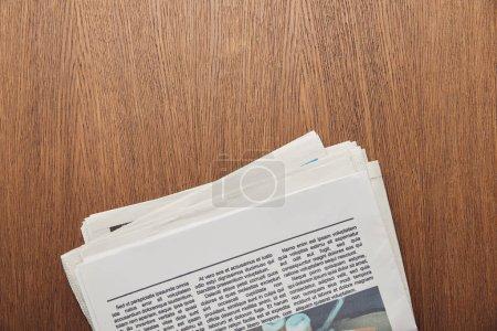 Photo pour Vue de dessus du journal avec article sur la surface en bois - image libre de droit