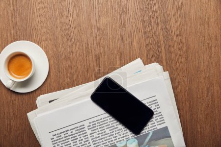 Photo pour Vue du haut du journal près de tasse avec café et smartphone avec écran blanc - image libre de droit