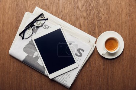 Photo for Top view of newspaper near cup with coffee, digital tablet with blank screen and glasses - Royalty Free Image