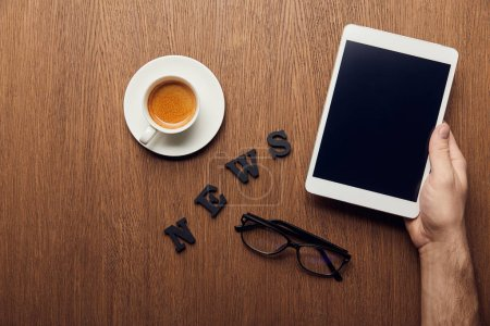 Photo for Cropped view of man holding digital tablet with blank screen near news lettering, cup of coffee and glasses - Royalty Free Image