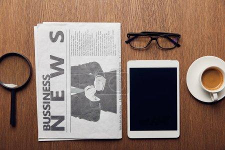 Photo pour Vue de dessus de la loupe près de journal, tasse à café, une tablette numérique avec écran blanc et verres - image libre de droit