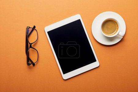 top view of digital tablet with blank screen near cup of coffee and glasses on orange