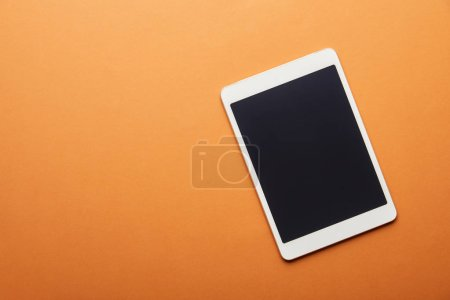 top view of digital tablet with blank screen isolated on orange