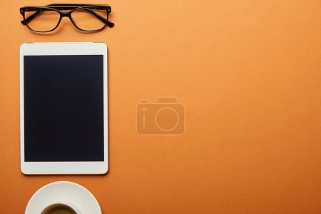 Photo for Top view of digital tablet with blank screen near cup and glasses isolated on orange - Royalty Free Image