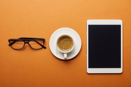 Photo pour Vue de dessus de tablette numérique avec écran blanc près de coupe avec boisson et verres sur orange - image libre de droit