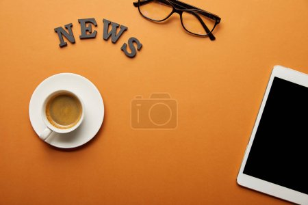 top view of digital tablet with blank screen near glasses, news lettering and cup of coffee on orange