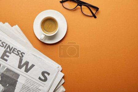 Photo pour Vue de dessus des lunettes près du journal d'affaires et tasse de café sur orange - image libre de droit