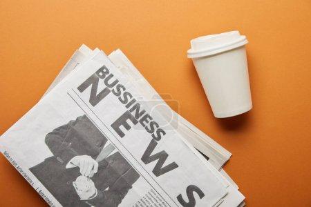 Photo pour Vue du haut du journal d'affaires près de tasse en papier avec boisson sur orange - image libre de droit