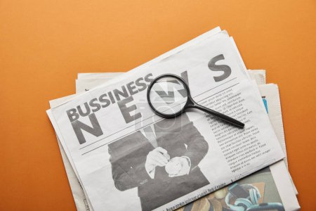 Photo for Business newspaper near magnifying glass on orange - Royalty Free Image