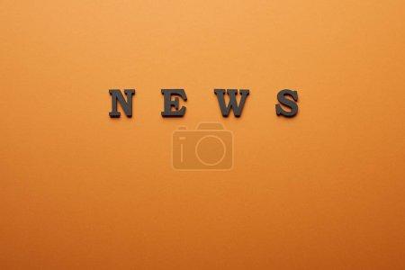 Photo pour Vue de dessus du lettrage de nouvelles avec espace copie sur orange - image libre de droit