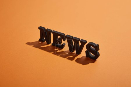 Photo for News lettering with copy space and shadows on orange - Royalty Free Image