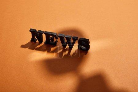Photo pour Lettrage d'actualité noir avec espace de copie près des ombres sur orange - image libre de droit