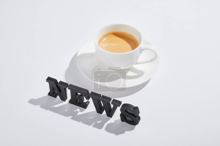 Photo for Black news lettering near cup with drink on white - Royalty Free Image