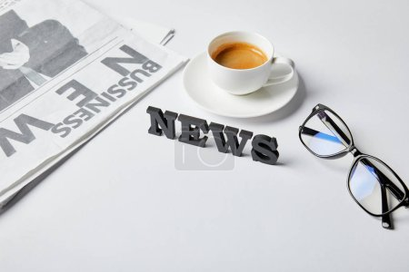 Photo for News lettering near cup of coffee, glasses and business newspaper on white - Royalty Free Image