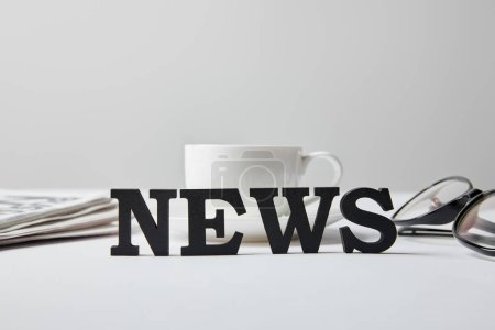 Photo for Selective focus of news lettering near cup of coffee, glasses and newspaper on white - Royalty Free Image