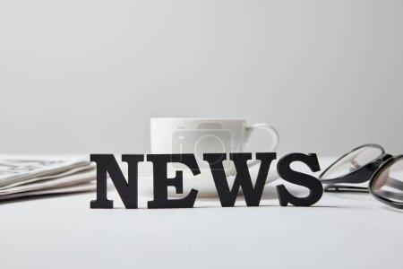 Photo pour Foyer sélectif de nouvelles lettrage près de tasse de café, verres et journal sur blanc - image libre de droit